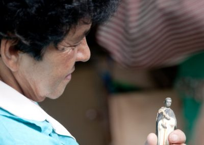 Clotilde Alvarado (70) looks at figure of a saint that she had pulled out of the destroyed house where she was born.